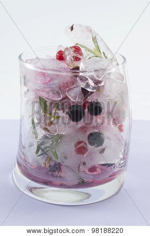 Red Forest Fruit Cocktail With Ice, Lemon And Sliced Fruits In A Crooked Glass