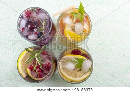 Four Non Alcoholic Fruit Cocktails Arranged On The Green Table Top View