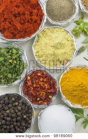 Close Up Of Different Spices In Shiny Bowls On A White Wooden Table