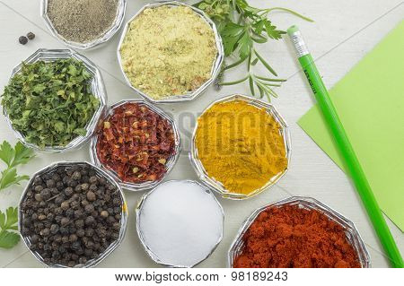 Various Spices In Shiny Bowls With Pen And Paper For Writing Recipes On A White Wooden Table