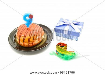 Donut With Nine Years Birthday Candle, Whistle And Gift On White