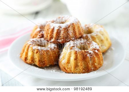 Bundt Cakes On Plate On White Wooden Background