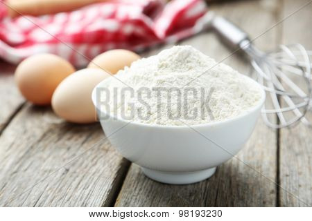 Bowl of wheat flour with eggs and whisk on grey wooden background