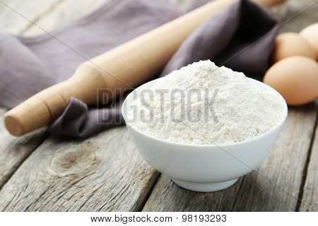 Bowl Of Wheat Flour With Eggs And Rolling Pin On Grey Wooden Background
