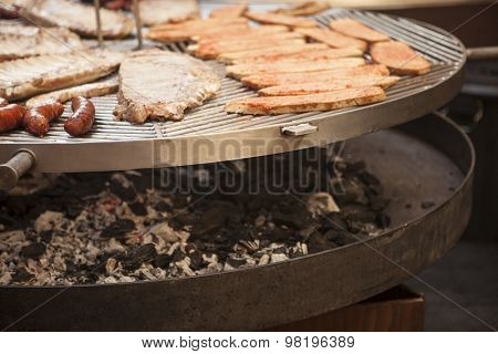 Gourmet meat pieces pork ribs, sausages,on a large grill in Spain.