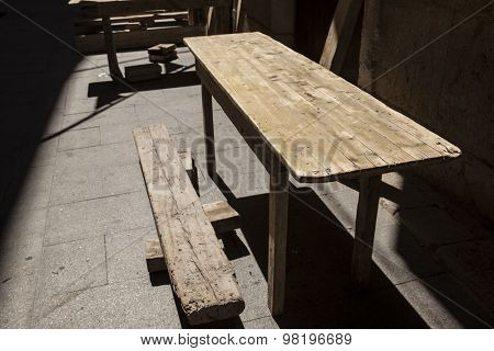 Old wooden tables at an outdoor cafe in Spain