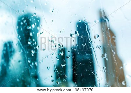 Silhouettes Of Building Towers Behind Wet Glass