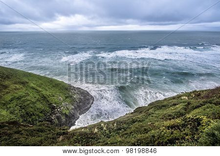 Ocean wave hitting the shore before rain