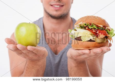 Young fit man is making decisions about food