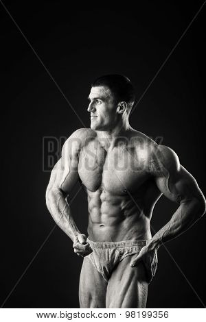 Man posing on a black background, shows his muscles.