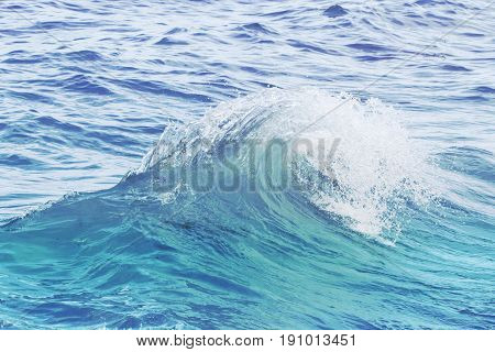 poster of Turquoise blue wave on rippled sea water. Sea water closeup photo. Sea wave swirl. Surfing in seashore. Clean wave splash. Seaside vacation concept. Marine scene or background. Wave curl with spray