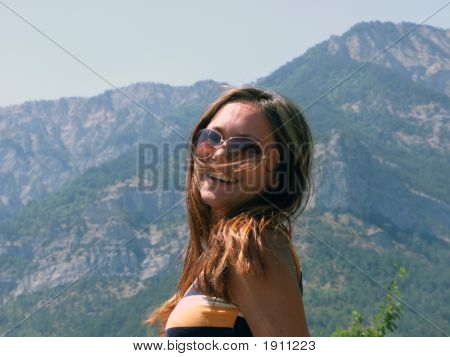 Portrait Of The Smiling Beautiful Girl On A Background Of Mountains