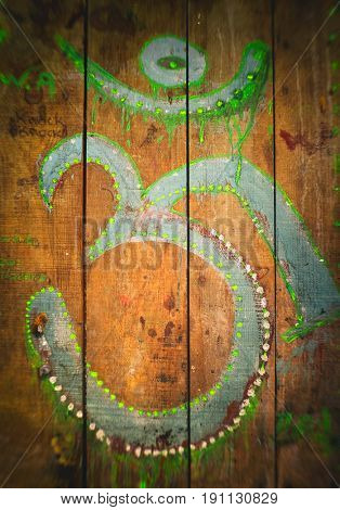 Om sign roughly painted green on an old wooden surface