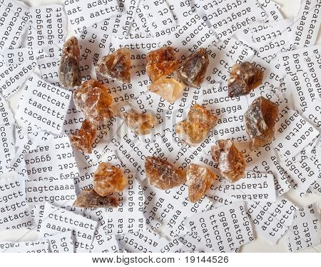 Brown crystal sugar with a background of a tore DNA sequence