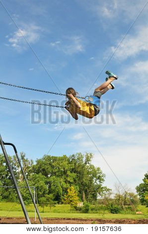 Young girl on swing against a blue sky
