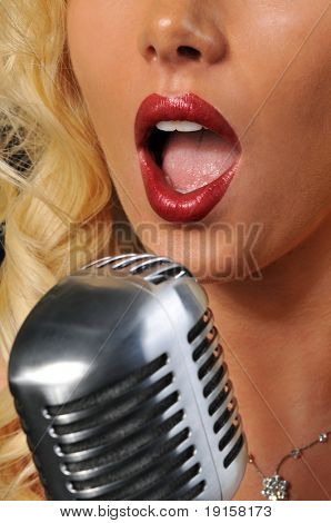Young woman singing into a microphone with focus on the singer