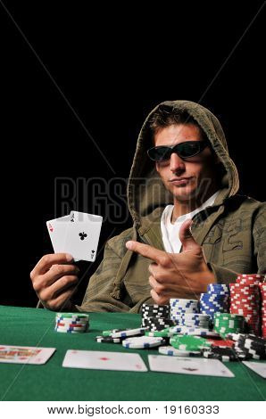 Young man playing poker and holding a couple of aces against a black background