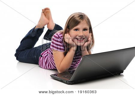 Little Girl with laptop computer lying on the floor isolated on white