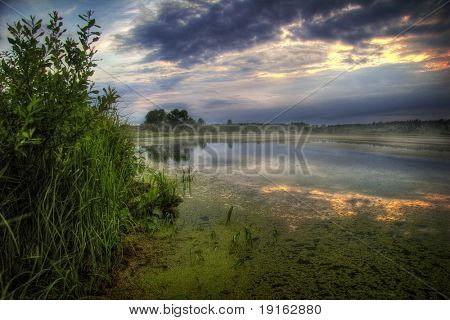 Misty sunset around lake. It is photographed in Russia. 60 kilometers from Moscow. The end of summer.