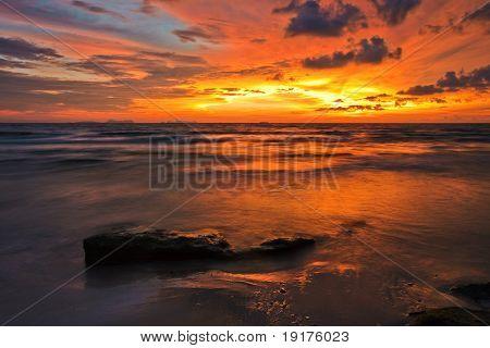Fantastic tropical sunset on the stones beach. Lanta island. Thailand