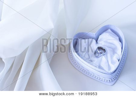 Two wedding ring in the heart shaped box in blue tones