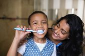 Close up portrait of girl brushing teeth with mother in bathroom poster