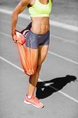 Low section of female athlete stretching leg on sports track during sunny day poster