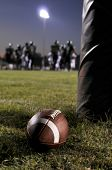 pic of football field  - Football at the field with an ongoing game as background - JPG