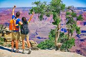 Grand Canyon hikers tourists couple cheering success with arms up happy for hike achievement. Backpa poster