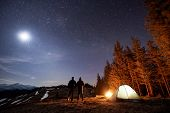Two Male Hikers Have A Rest In His Camp Near The Forest At Night. Men Standing Near Campfire And Ten poster