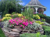 stock photo of gazebo  - A colorful landscape with flowers a bright sky and gazebo - JPG
