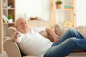 Fat senior man watching TV while lying on sofa at home. Sedentary lifestyle concept poster