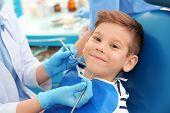 Dentist examining little boys teeth in clinic poster
