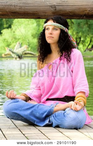 photograph of a beautiful hippie woman meditating on the river beach