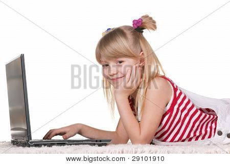 Smiling Girl Studying With Laptop Lying On The Thick Carpet