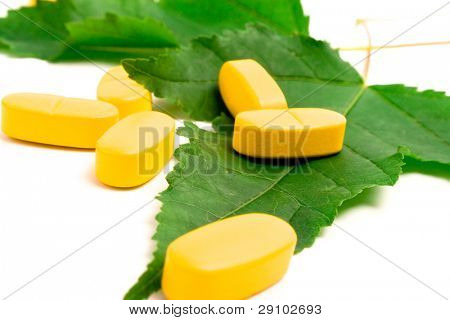 yellow vitamin pills over green leaves on white background