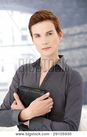 Determined businesswoman standing in office holding organizer, looking at camera.?