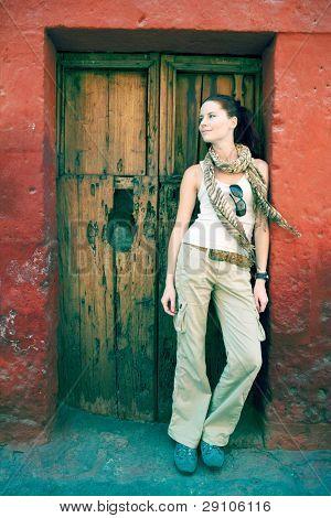 Female turist at front of old door, Cuzco, Peru.