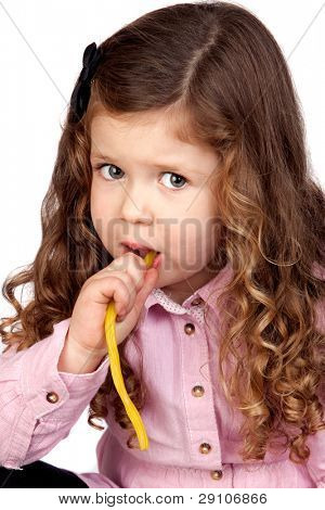 Adorable baby with pink shirt eating goodies isolated over white background