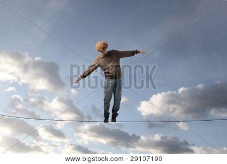 junger Mann seine Balance zu halten über ein Kabel