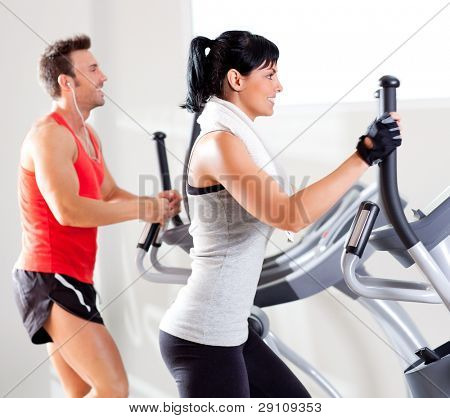 Mann und Frau mit Cross-Ellipsentrainer in Sport-Fitness-Fitness-club