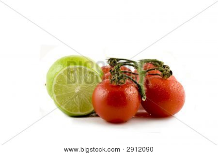 Two Limes And Two Tomatos Isolated On White Background