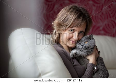 Woman Sitting On The Couch And Fondles Gray Cat