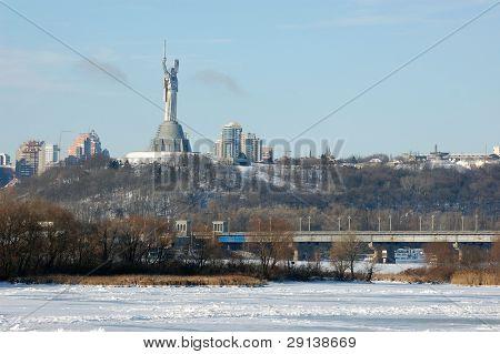 Monumento de la victoria y el puente sobre el río Dniéper en vinter. Kiev, Ucrania