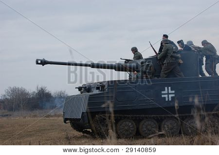 VINNITSA, UKRAINE - MAR 21: Members of history club called Red Star wear historical German uniform on the tank as they participate in a WWII reenactment in Vinnitsa, Ukraine on March 21, 2009.