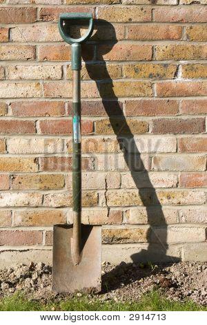 Spade gegen Gartenmauer
