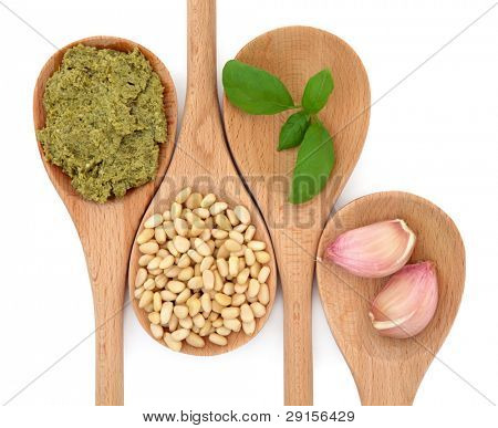 Pesto sauce and ingredients of pine nuts, basil herb leaf and garlic cloves in wooden spoons isolated over white background.