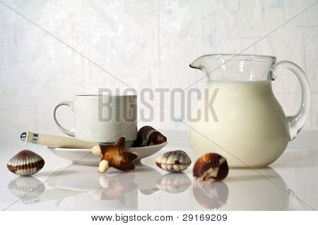 White cup, milk and sweets