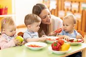 Babysitter Feeding Nursery Babies. Toddlers Eat Healthy Food In Daycare Center poster
