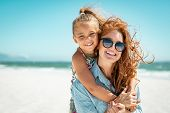 Smiling mother and beautiful daughter having fun on the beach. Portrait of happy woman giving a pigg poster